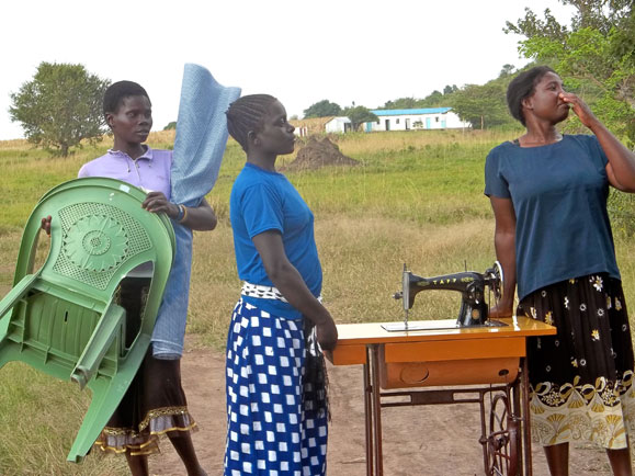 women carrying the machines/fabric, etc. to the church to open the academy